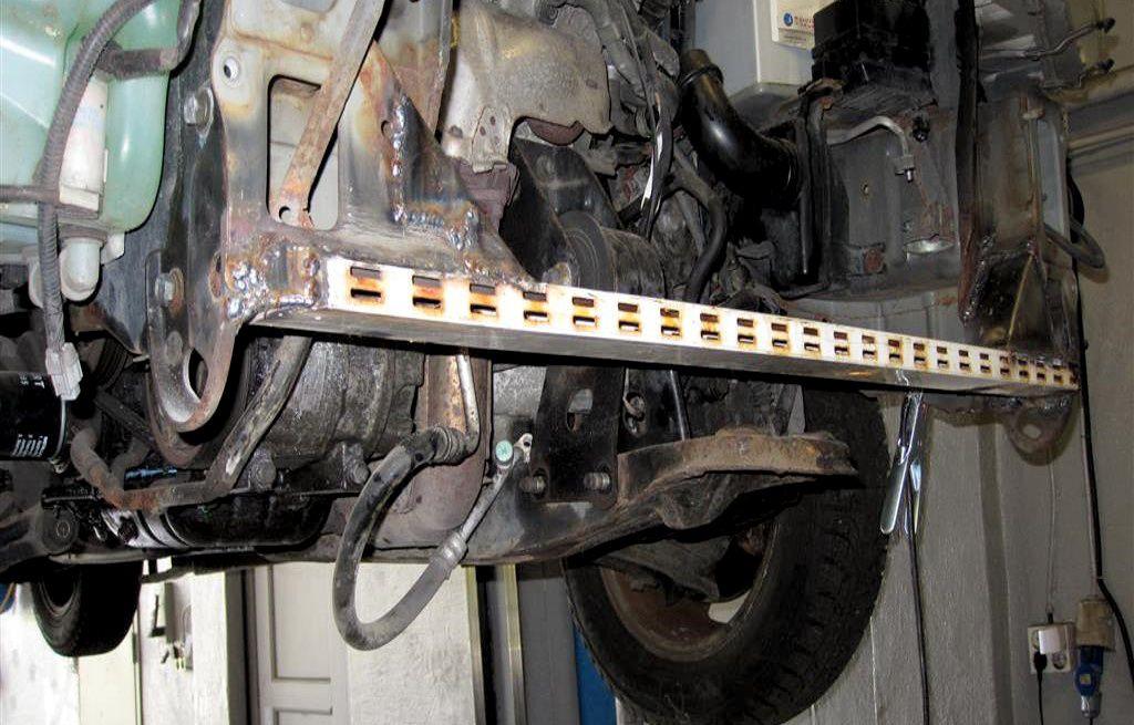 KREATIV, MEN FARLIG LØSNING: Her har et verksted ifølge Statens vegvesen brukt en hyllereol i reparasjonen av en bil.