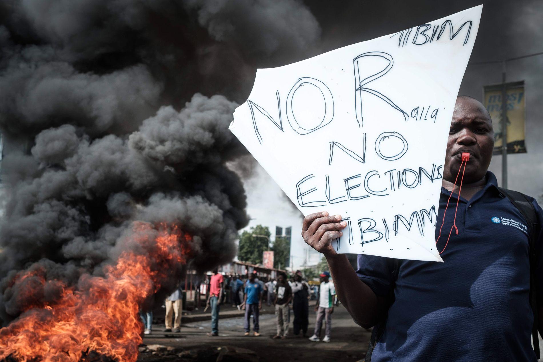I FYR OG FLAMME: En demonstrant i Kisumu, Kenya, viser støtte til opposisjonen under en protest 11. oktober mot påstått valgfusk i forbindelse med valget 8. august.