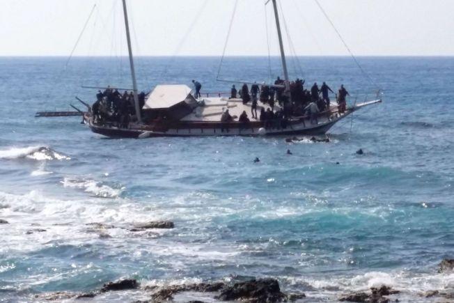 NÆR LAND: Mens noen svømmer mot land klamrer andre seg fast til båten. Båten kom fra Tyrkia, men det er ikke kjent hvilke nasjonaliteter som var om bord.