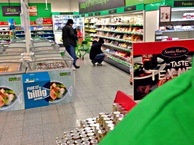 TOK FELLE-BILDE: Dette er ifølge Kiwi enhver.nos prisjeger (sittende på huk) mens han sjekket prisene i Kiwis butikk ved Mølla i Oslo tirsdag ettermiddag. Foto: Kiwi.
