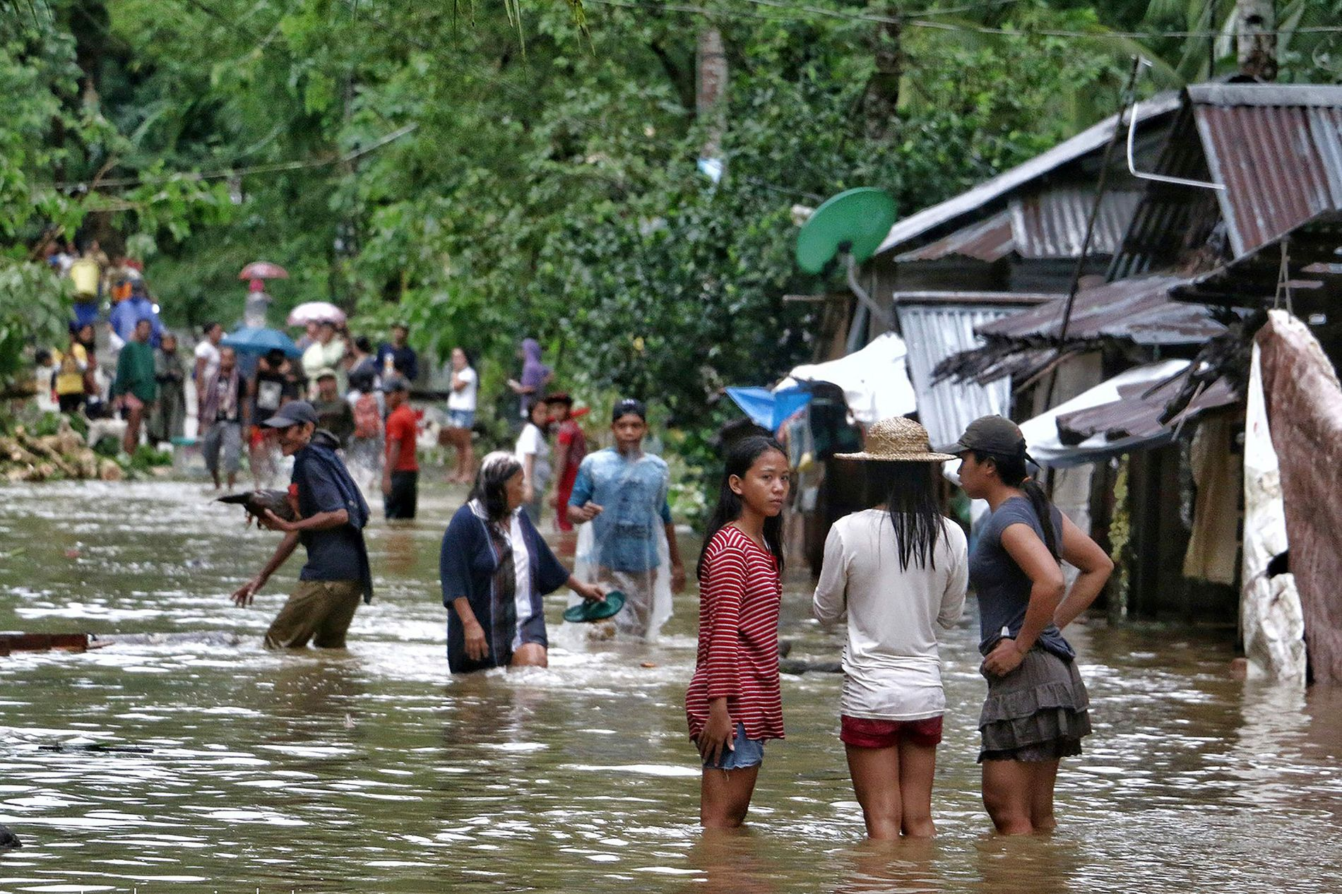 EVAKUERES: Innbyggere i Brgy Calingatngan krysser en oversvømmet gate i Øst-Samar på Filippinene lørdag.
