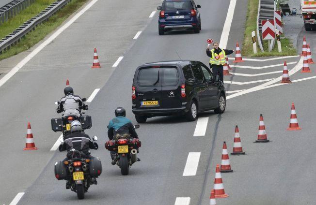 SKJERPER KONTROLLEN: Politiet dirigerer trafikk langs motorveien A8 ved byen Piding helt sør i Tyskland mandag.