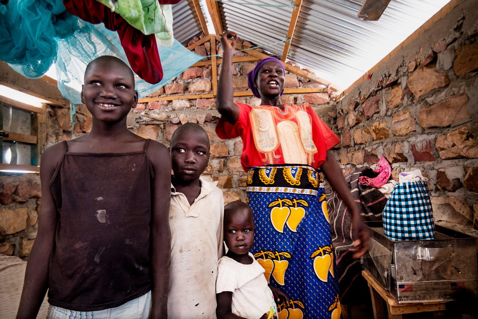 I NY LEIR: Cecilia (34) flyktet alene fra Sør-Sudan med sine fire barn, her med Quinen (11), Gabriel (8) og Sandy (3). Hun bor i en av de nye husene i den nye «byen» UNHCR bygger.