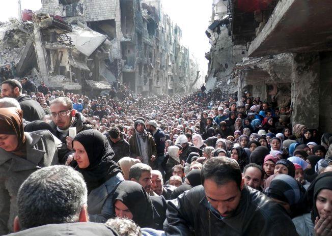 STORE LIDELSER: Syrere står i kø for å motta subsidiert mat fra hjelpearbeidere i Damaskus, Syria. Bildet er tatt 31. januar 2014.