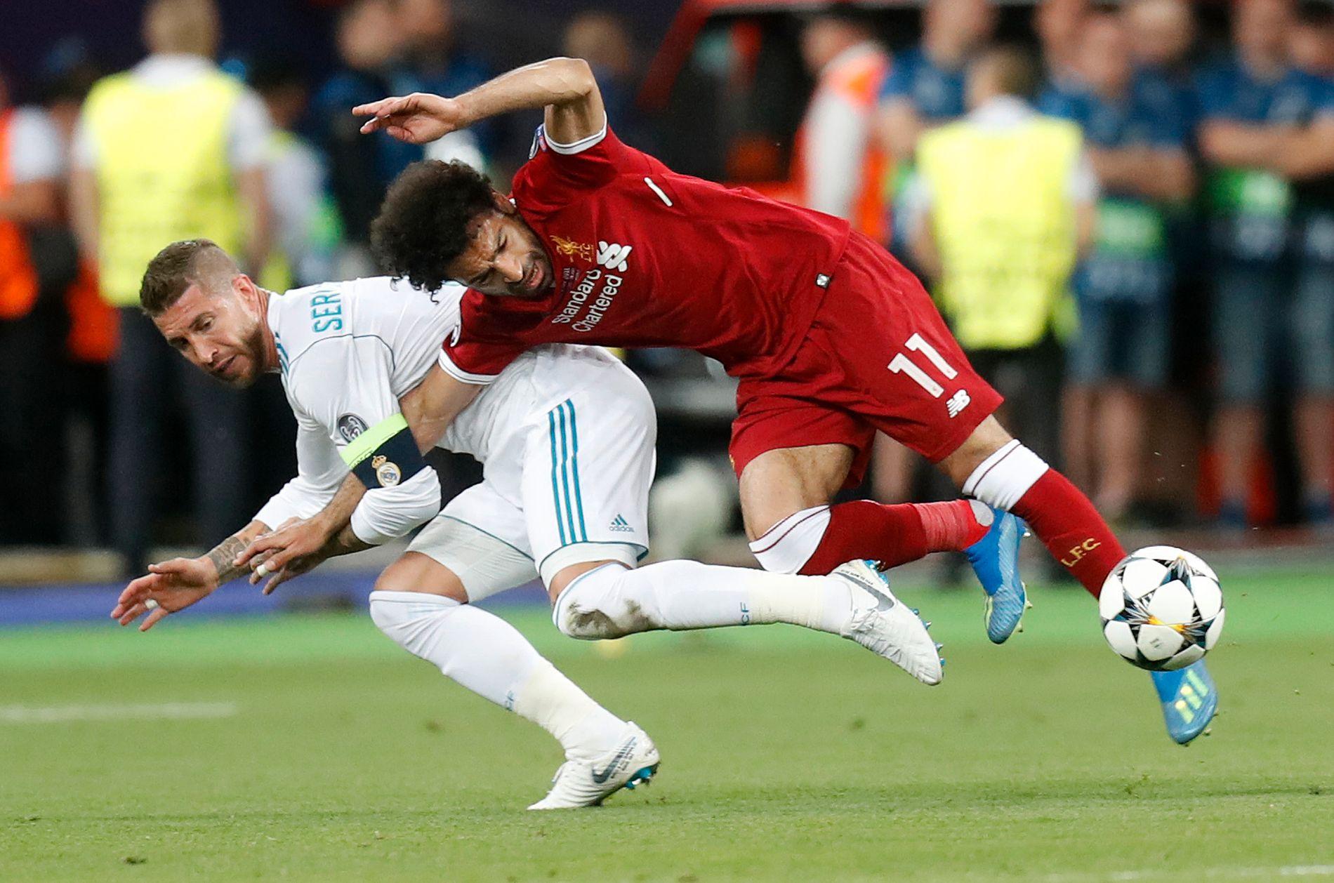 SKADET SEG: Mohamed Salah (høyre) dras i bakken av Sergio Ramos under Champions League-finalen i mai.