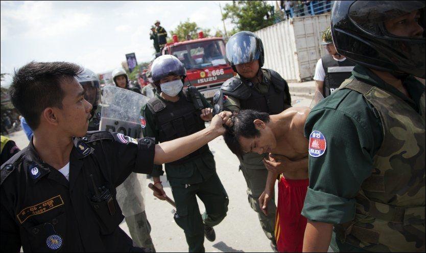DEMONSTRERTE: Kambodsjansk opprørspoliti pågriper en tekstilarbeider som demonstrerer mot myndighetene. Foto: Reuters / NTB scanpix