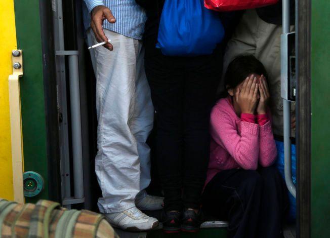 TRAGISK: Hun skjuler ansiktet i hendene og gjemmer seg litt for alt det fryktelige som skjer rundt henne. Situasjonen er svært vanskelig for flytkningene som har blitt sittende fast i Ungarn, spesielt vanskelig er det å være barn.