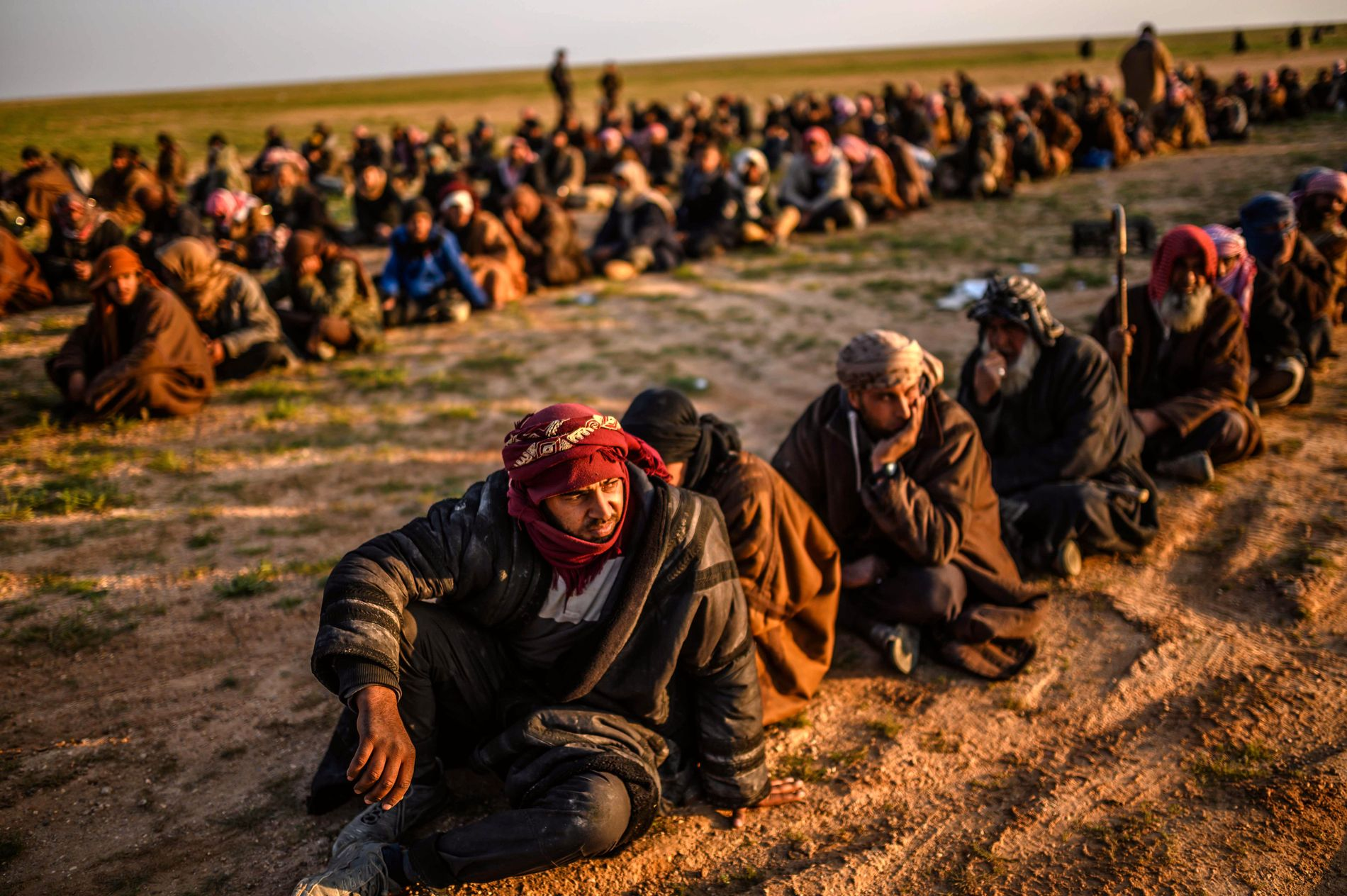 ANHOLDES: Mistenkte IS-krigere venter på å bli ransakt av kurdiske SDF, etter å ha forlatt IS' siste utpost.