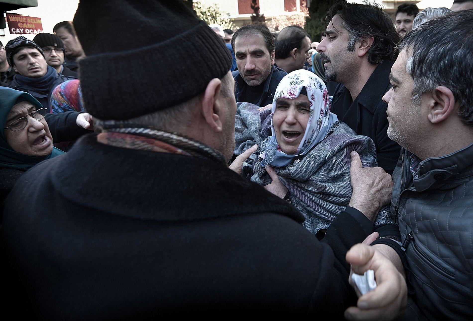OPPLØST I TÅRER: Moren Ayten hjelpes gjennom mengden av sørgende av sønnen Mehmet (til høyre) under begravelsen.
