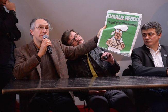 «KEEP CALM AND CHARLIE ON»: Charlie Hebdo-redaktør Gerard Briard, tegner Renald «Luz» Luzier og journalist Patrick Pelloux viste frem den nyeste utgaven av satiremagasinet under en pressekonferanse tirsdag.