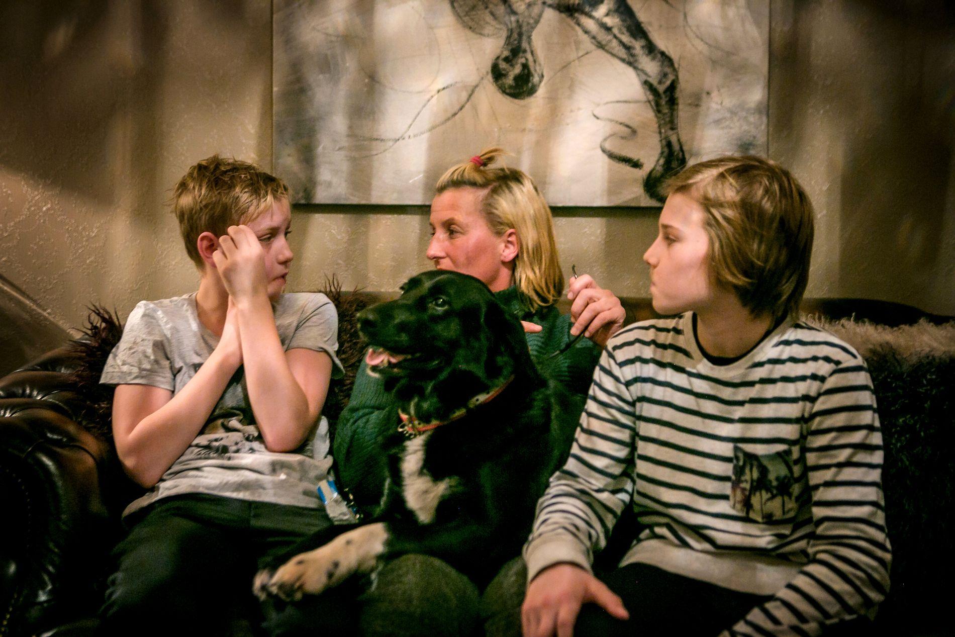 TOMROM: Den åtte år gamle hunden Ludvig ble drept av ulv natt til søndag. Mari Gerhardsen (i midten) sitter igjen med et tomrom, og merker at hundene Phoebe (15) og Lotus (4) reagerer på at Ludvig er borte. Her er Mari sammen med Lucas Waaler (14), Linus Waaler (11) og Lotus i sofaen hjemme.