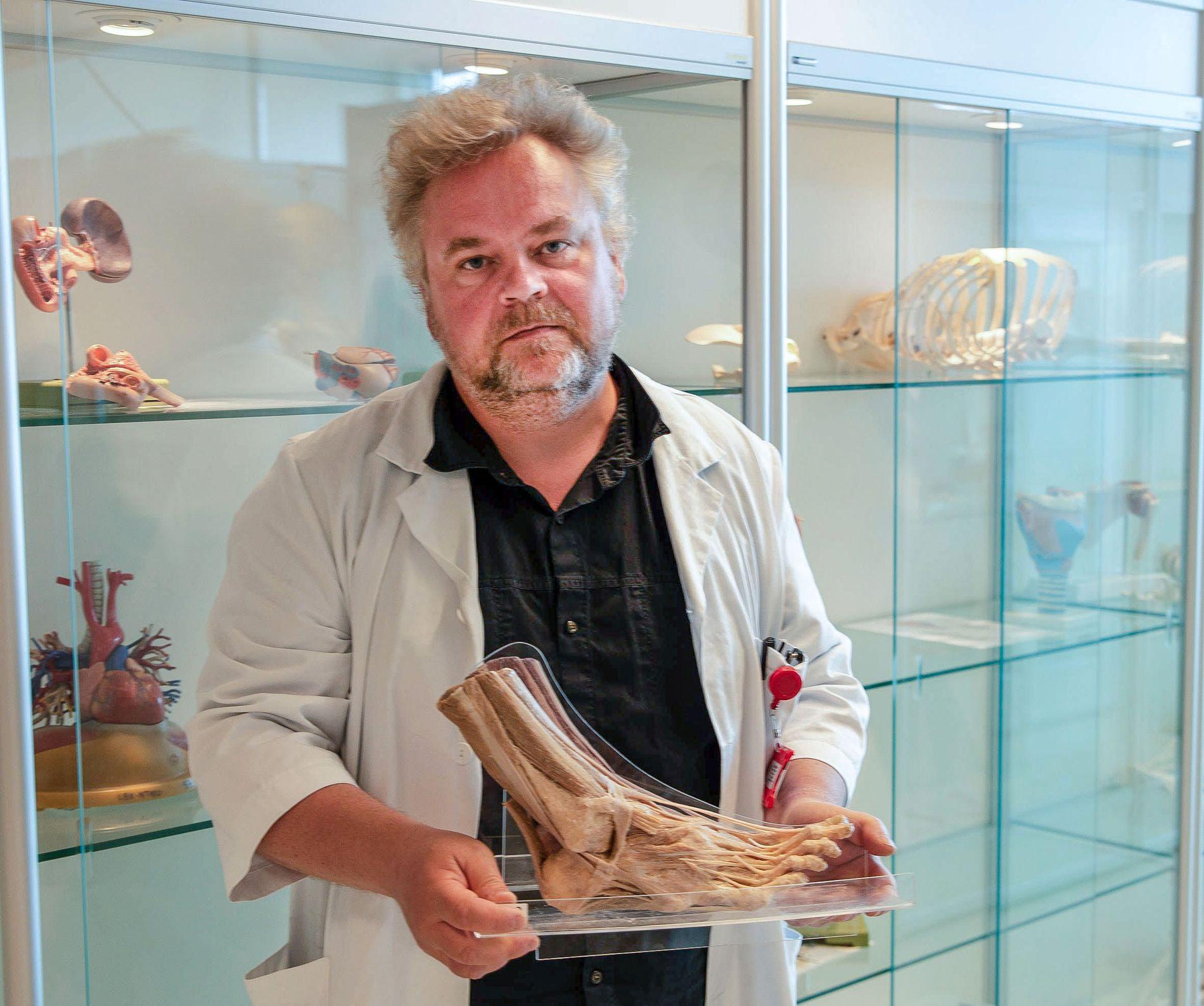 HAVNET I KLESVASKEN: Det var en balsamert fot av denne typen som ble funnet i vaskemaskinen til vaskeriet Nor Tekstil i Trondheim. Foten blir holdt av instituttleder Torstein Baade Rø.