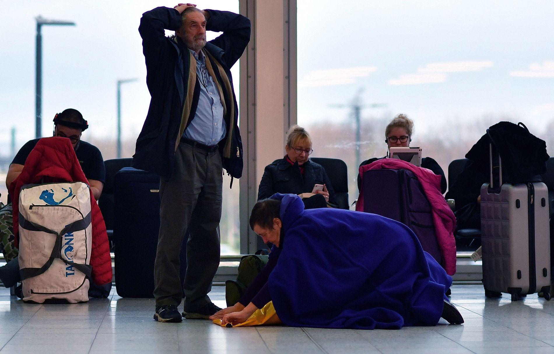 OPPGITTE PASSASJERER: Flypassasjerer ventet i timesvis på Gatwick-flyplassen ved London fredag. En dame legger seg ned for å hvile på gulvet, mens andre fordriver tiden med lesing og mobil-sjekking.