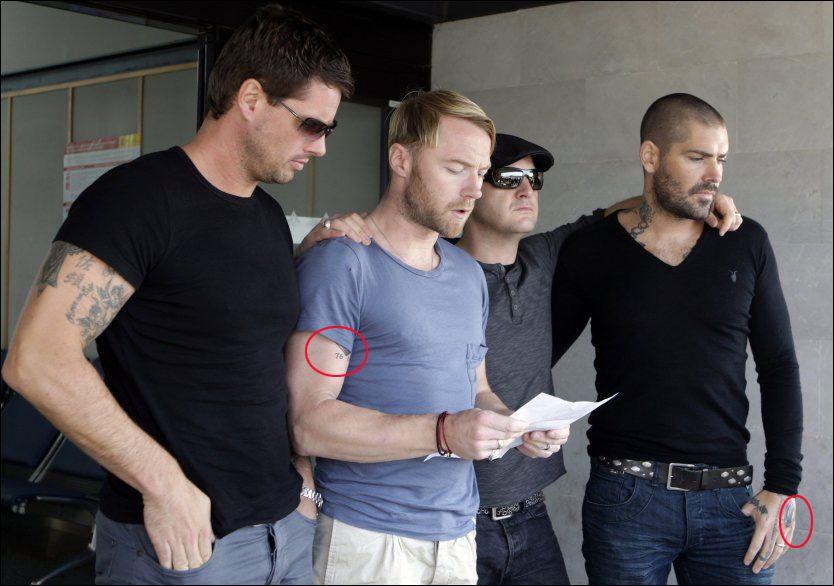 PÅ FLYPLASSEN: Ronan Keatings (t.v.) og Shane Lynchs (t.h.) tatoveringer kunne ses da de fire resterende Boyzone-medlemmene fløy fra Mallorca til Dublin med avdøde Stephen Gately fredag. Foto: Reuters