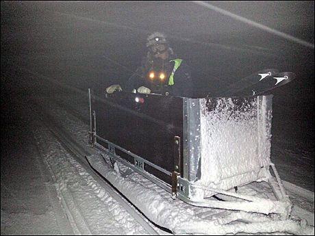 TRANSPORT: Det er veldig dårlig vær i området, og letemannskaper fraktes ut med snøscooter. Foto: NORSKE REDNINGSHUNDER