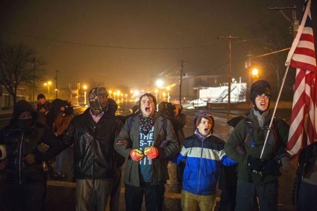 FORSØKTE Å SPERRE VEI: Demonstranter forsøkte i natt å sperre av en vei i Ferguson, men ble raskt stoppet av politiet.