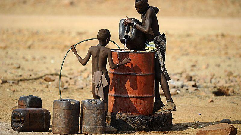HOLDES NEDE: I det fattige land klarer å selge noe til Norge, slår en rekke uheldige begrensninger inn, mener Henrik Aasheim. På bildet heller to gutter vann i en tank 20. august 2010 i landsbyen Okapare, i det nordlige Namibia.