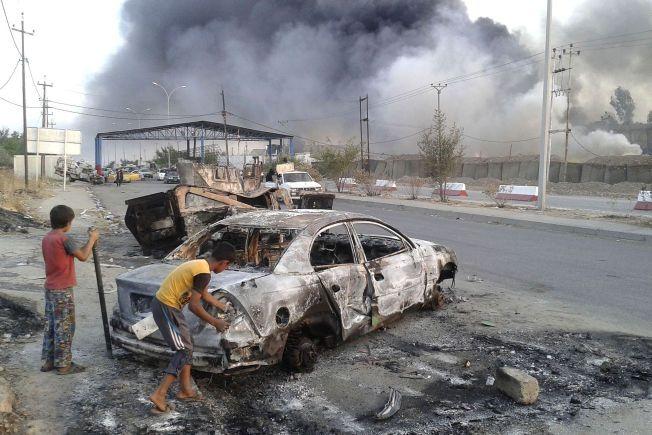 PÅ AVSTAND FRA VOLDEN: To gutter leker med en utbrent bil utenfor Mosul under kampene mellom den islamistiske gruppen ISIL og irakiske regjeringsstyrker.