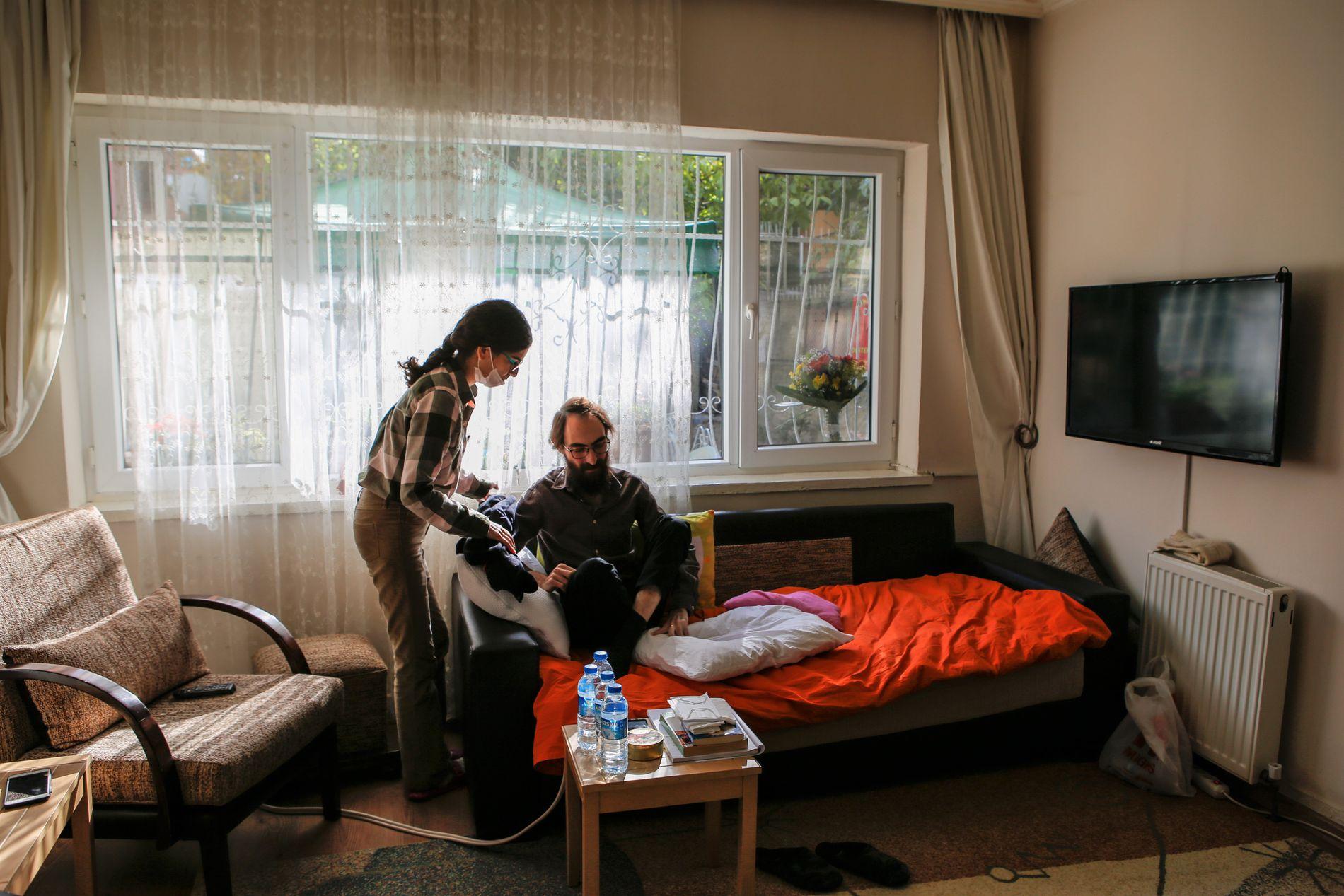 ISOLASJON: Kona Esra (28) hjelper Semih Özakça (28) å finne en komfortabel stilling i sofaen hjemme i Ankara. De er begge i sultestreik, og immunforsvaret er svakt.
