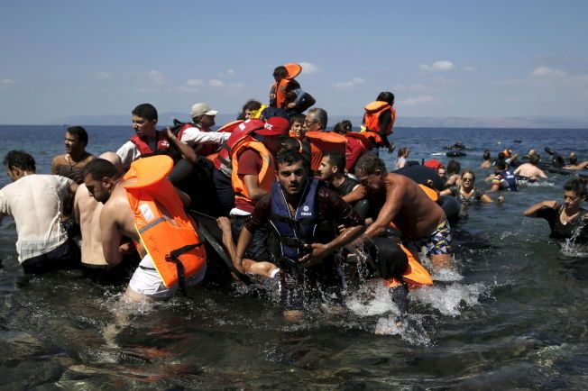 I SIKKERHET: Syriske og afghanske flyktninger hjelpes i land av frivillige etter at båten deres sank hundre meter fra den greske øya Lesbos søndag. Det samme skjedde utenfor øya Farmakonisi lenger sør - der druknet 28 flyktninger.