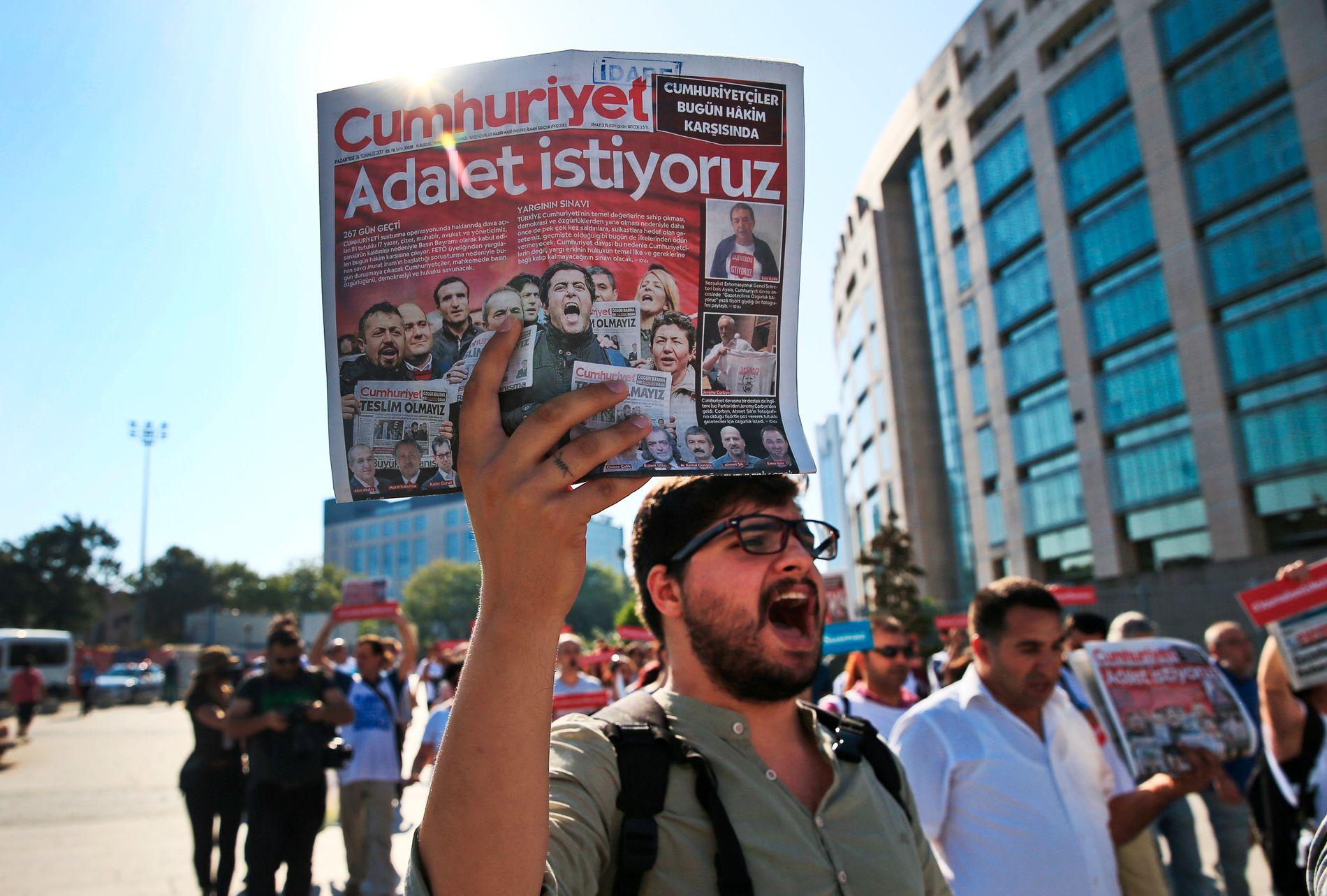 STØTTESPILLER: En aktivist som støtter avisen Cumhuriyet utenfor rettsbygget i Istanbul mandag. Avisen anses for å tilhøre venstresiden i Tyrkia, og for å støtte opp om sekulære verdier.