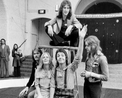 1972: Wings, med nylig avdøde Henry McCullough ytterst til høyre og Paul McCartney foran – med sin avdøde kone Linda McCartney til høyre for seg.