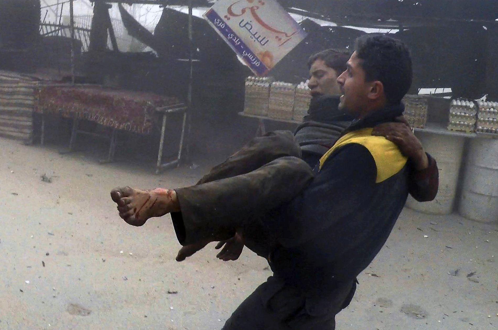 REDDER: Dette bildet, som nyhetsbyråer har fått fra organisasjonen White Helmets, skal vise en far bære sønnen sin etter et bombeangrep mot Øst-Ghouta.