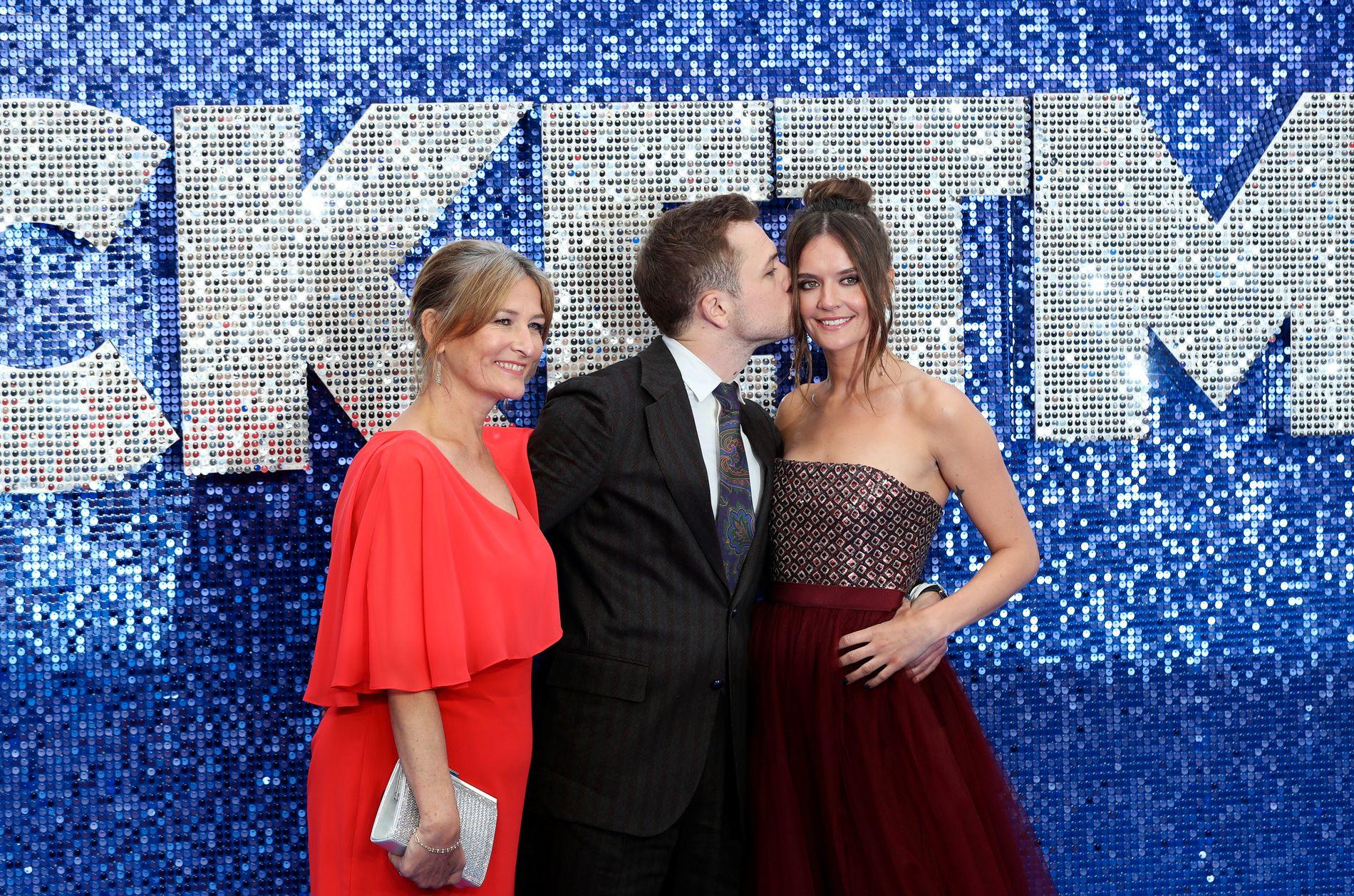 FAMILIE: Taron Egerton holder rundt moren Christine Egerton (t.v.) mens han kysser kjæresten Emily Thomas på London-premieren på «Rocketman» 20. mai.