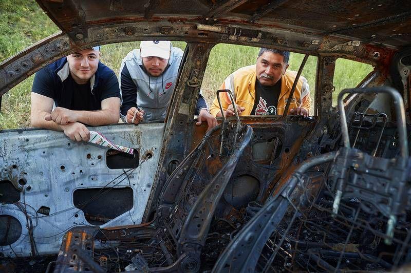 UTBRENT: Ungdomsarbeideren Hussein (t.v) står ved sin utbrente bil ved siden av kollegene Yosef og Juan.