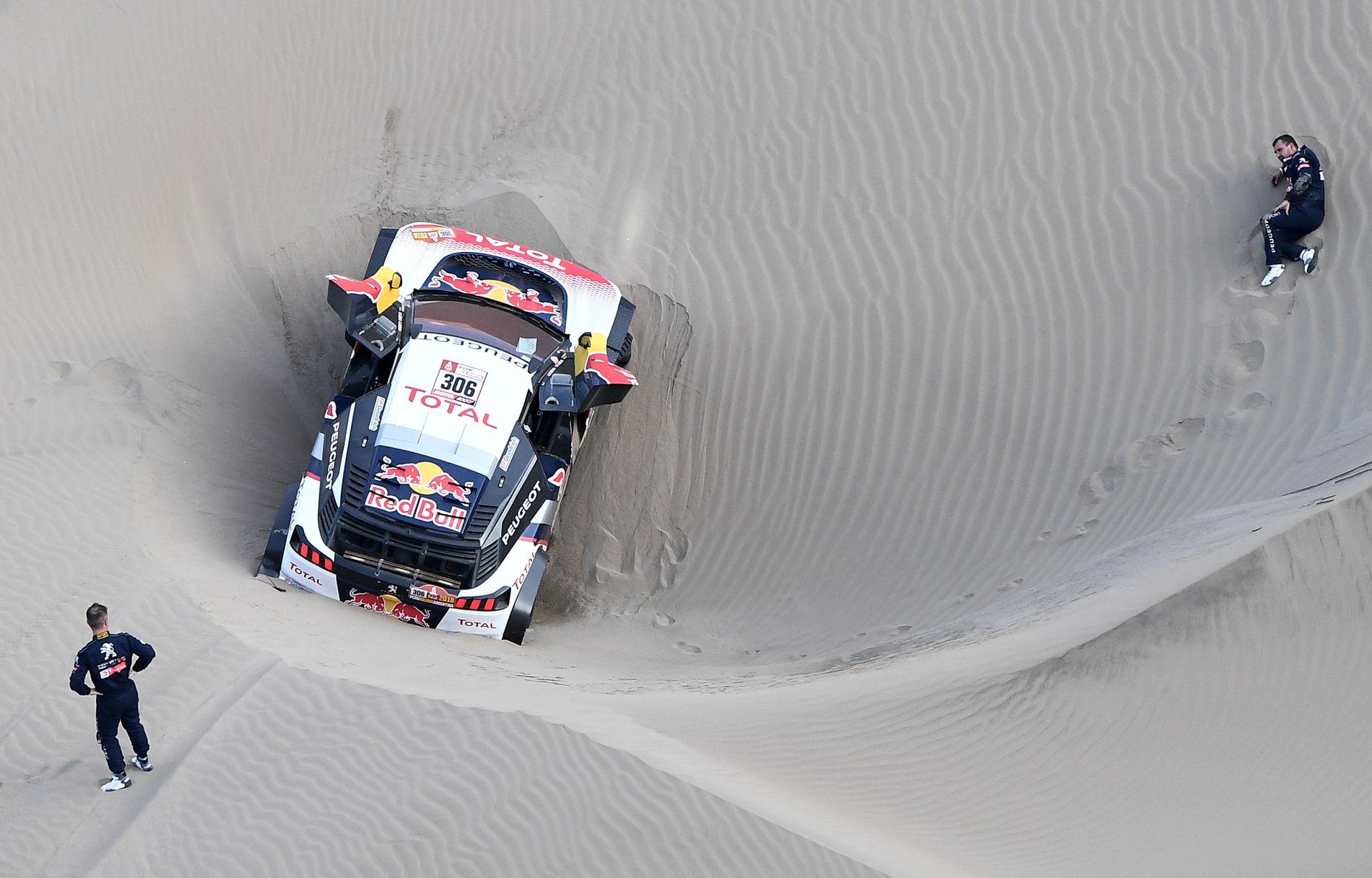 DRAMA: Sebastien Loeb (nederst) kikker oppgitt på bilen og registrerer at hans kartleser Daniel Elena (t.h.) ligger på sanden og har store smerter.