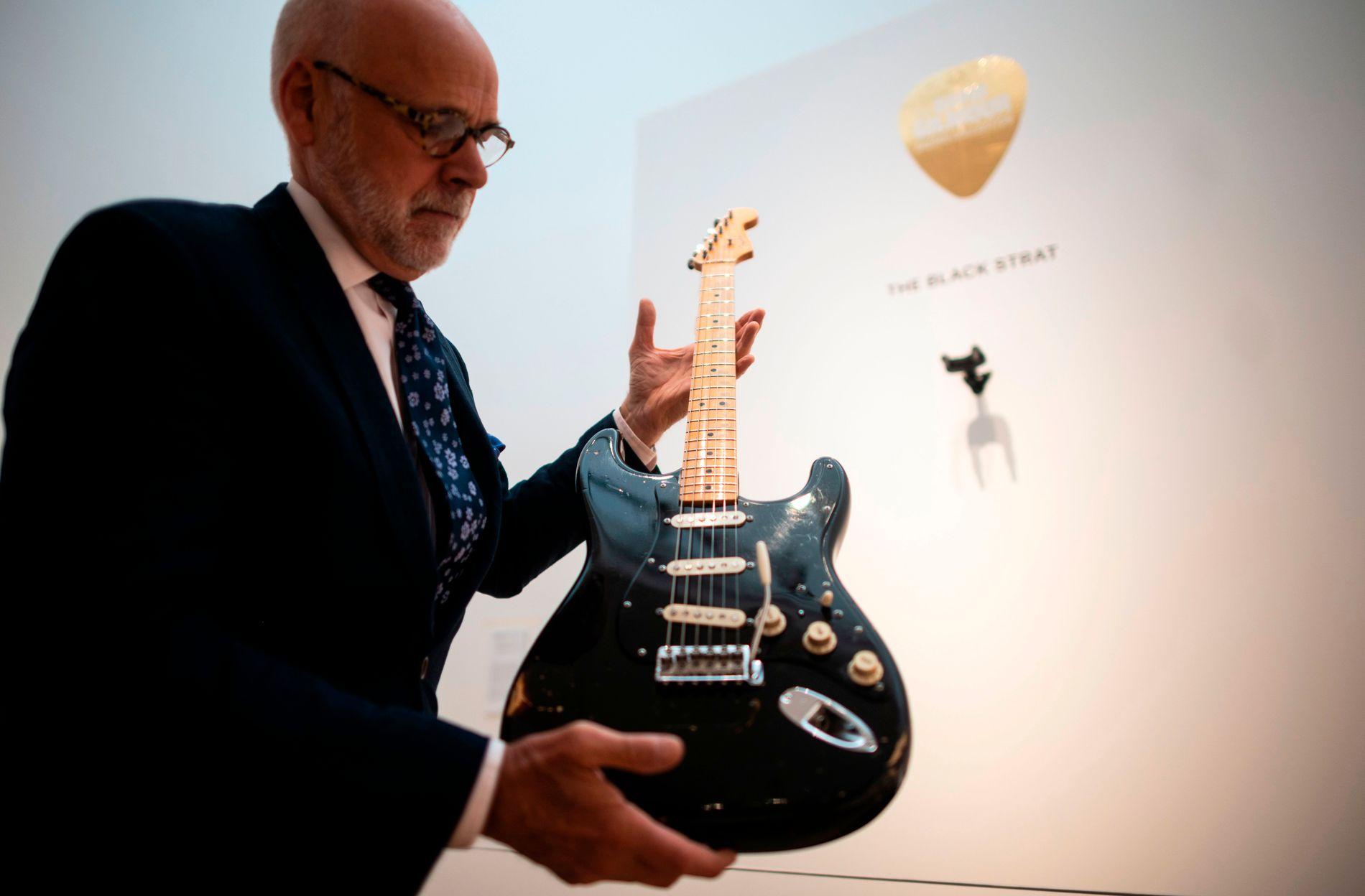 SOLGT: Musikkinstrument-spesialist Kerry Keane som holder «Black Strat»-gitaren til Gilmour.