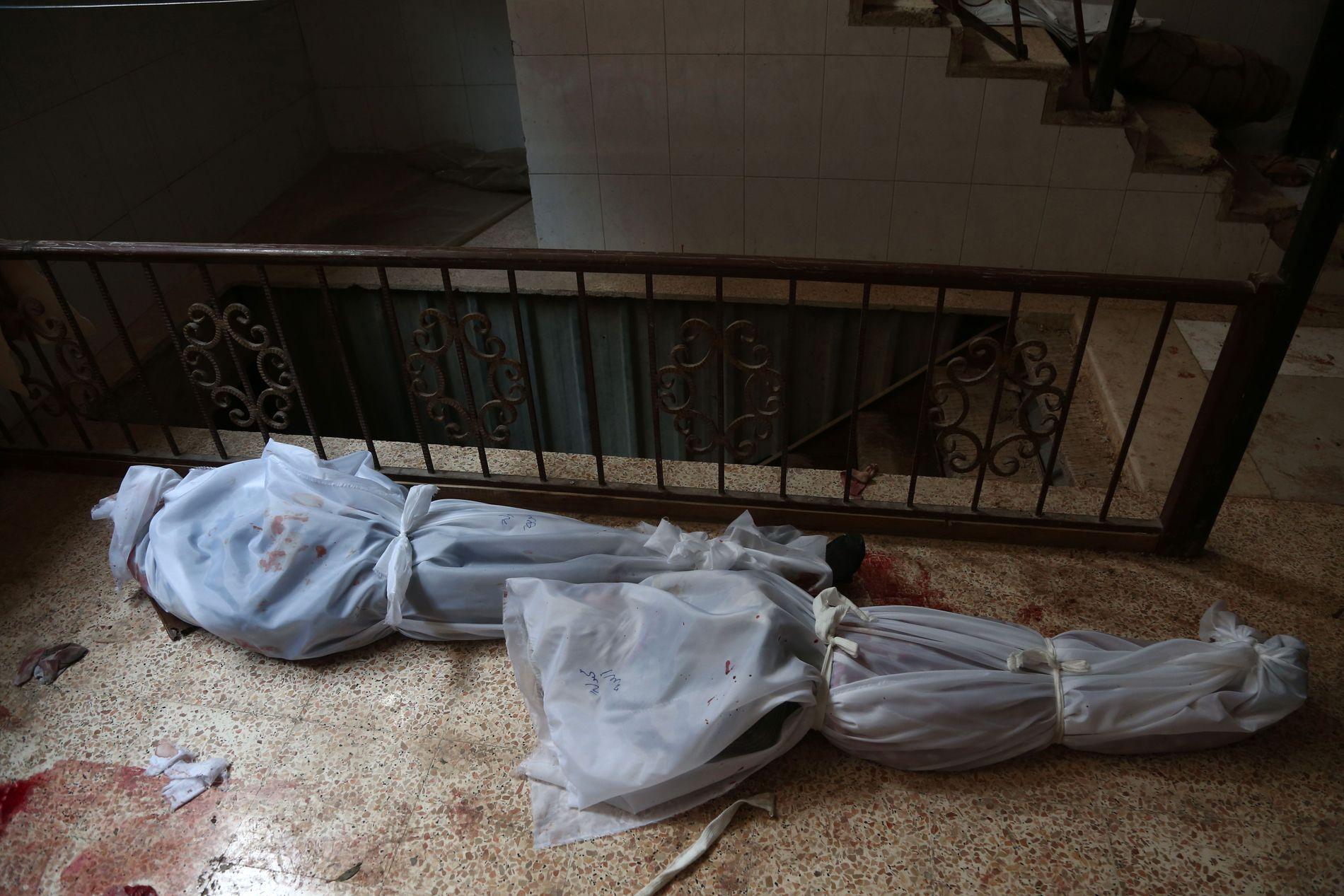 DREPT: Døde mennesker, drept i bombeangrep i Øst-Ghouta den 18. februar, fotografert av Abdulmonam Eassa i Hamouria.Foto: ABDULMONAM EASSA / AFP
