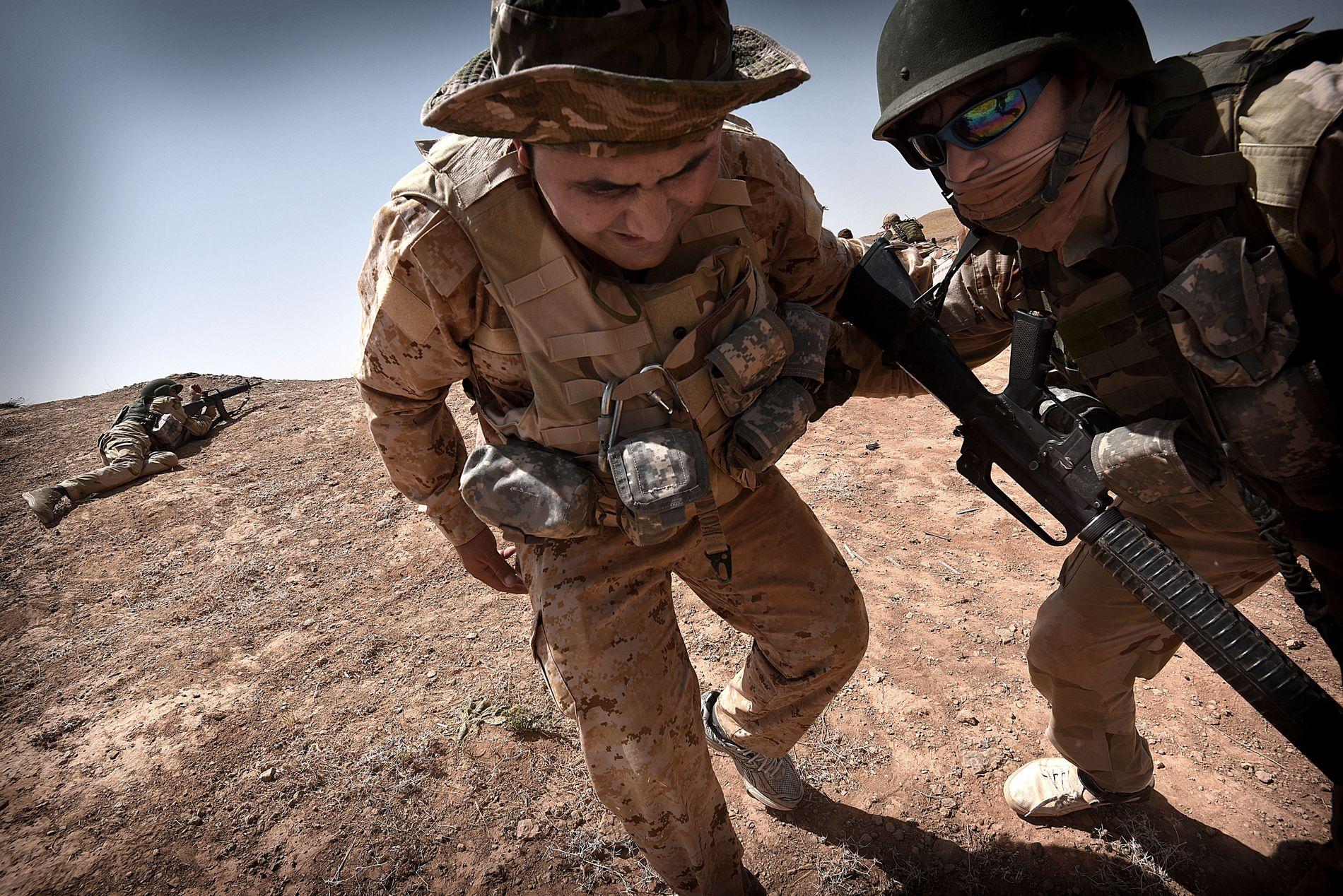 SPILLER SÅRET: Etter litt oppmuntring er de kurdiske peshmerga-soldatene med på øvelsen, der noen av dem skal spille såret og fraktes vekk fra kampsonen. Soldaten til venstre er blitt truffet i skulderen.