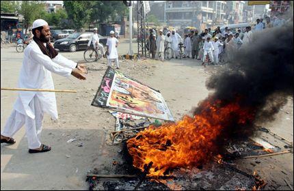 BRENNER DUKKER: Under demonstrasjoner i pakistan i dag ble det brent dukker av både Sir Salman og den dronning Elisabeth. Foto: AFP