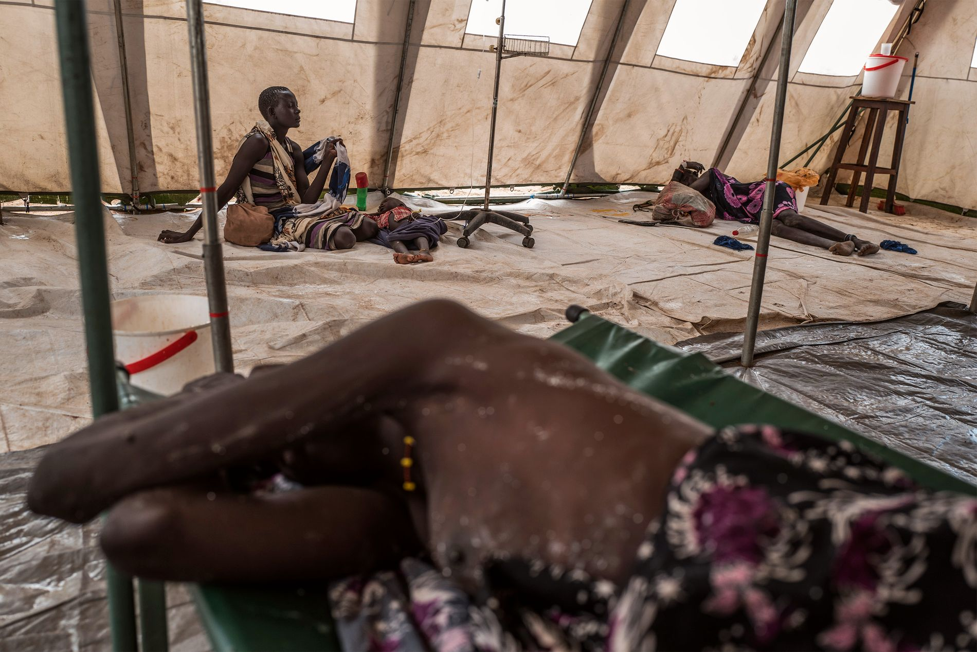 APRIL 2017: Hungersnød og epidemier truer Sør-Sudan. To kvinner og et barn fra Dinka-stammen får hjelp mot kolera i et teltsykehus i landsbyen Dor i provinsen Awerial. Foto: AFP