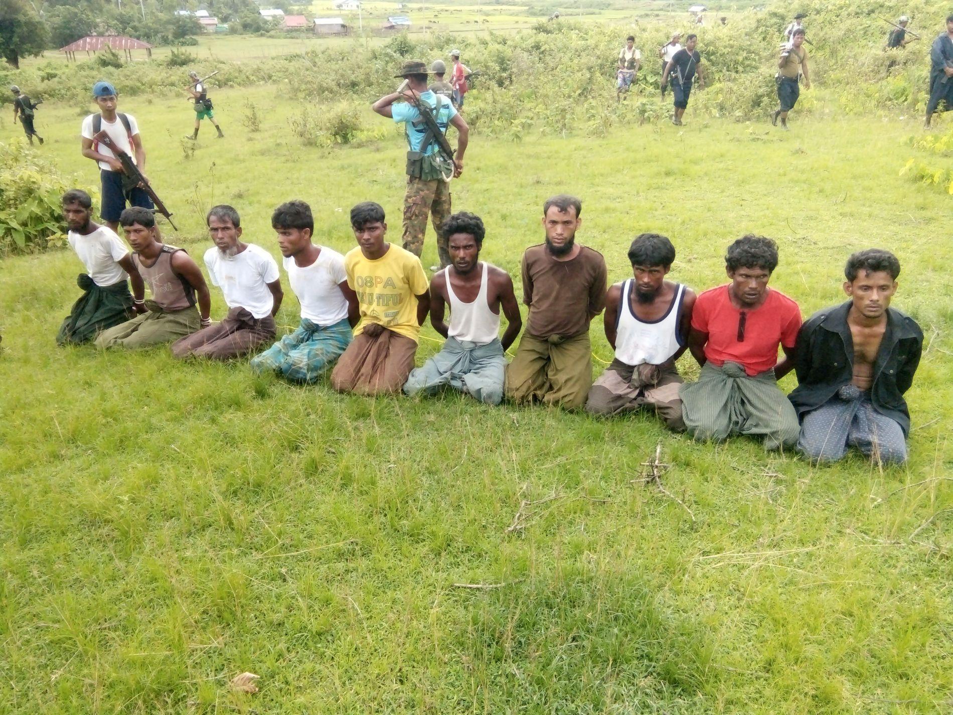 2. SEPTEMBER 2017: Rohingya-mennene fra den lille byen Inn Din i Rakhine-delstaten i Myanmar venter på henrettelsen, mens soldater fra landets sikkerhetsstyrker holder vakt.