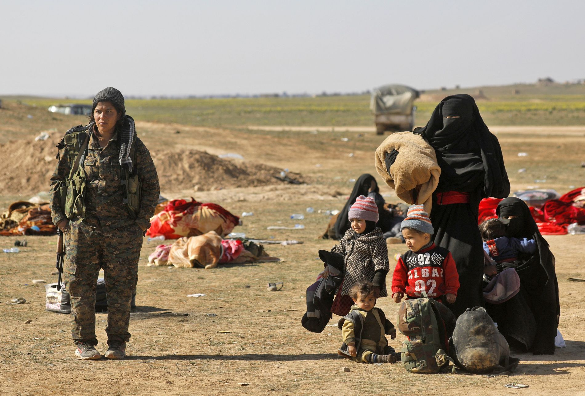 EVAKUERT: EN YPJ-kriger assisterer en kvinne og hennes barn kort tid etter at de er ute av Baghouz, som var IS sitt sitte tilholdssted i Syria. Bildet er tatt i februar.