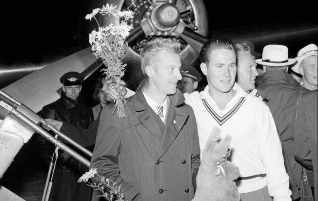 HYLLET: Ernst Larsen (til venstre) og spydkaster Egil Danielsen tas imot på Fornebu etter OL-medaljene i Melbourne i 1956.