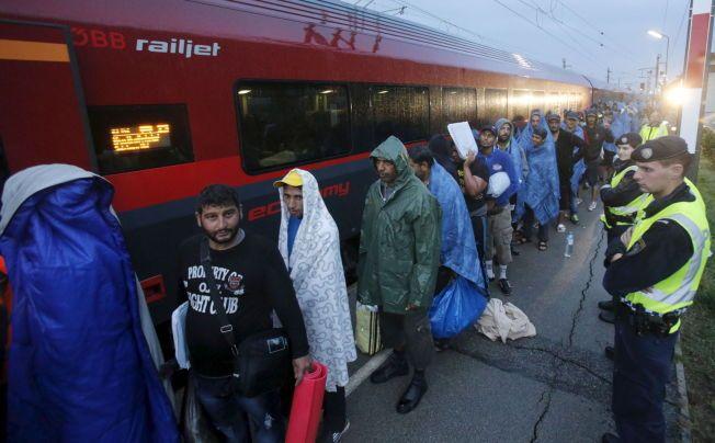 TYSKLAND NESTE: Flyktninger står i kø på stasjonen i Nickelsdorf i Østerrike, mens de venter på å gå om bord i toget mot Tyskland. Dette er målet for de fleste av de som i morges fikk krysse over grensen mellom Ungarn og Østerrike.