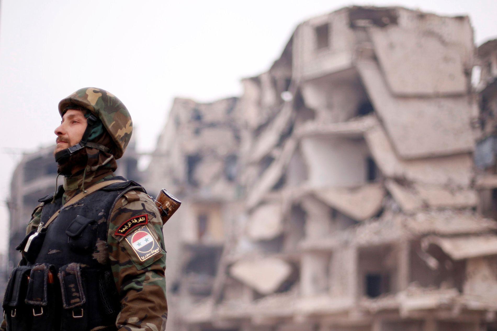 RUINER: Det er nesten bare ruiner igjen av Øst-Aleppo. Her står en av soldatene fra Syria's president Bashar al-Assads styrker, ved en av de bombede bygningene i Aleppo's Salaheddine distrikt. Foto: REUTERS/Omar Sanadiki