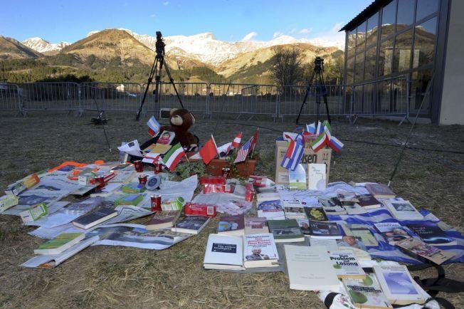 FLAGG: Ved foten av alpene i Seyne-les-Alpes minnes ofrene med flagg, bøker, blomster og bamse.