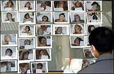 OMKOMNE: En politimann i Phuket sammenligner bildene av døde med bildene på pass som er levert inn. Foto: AFP