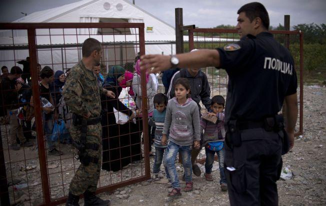 SENDES VIDERE: Grensevakter ved grensen mellom Hellas og Makedonia skysser flyktninger videre på et tog til Serbia tidligere denne uken.