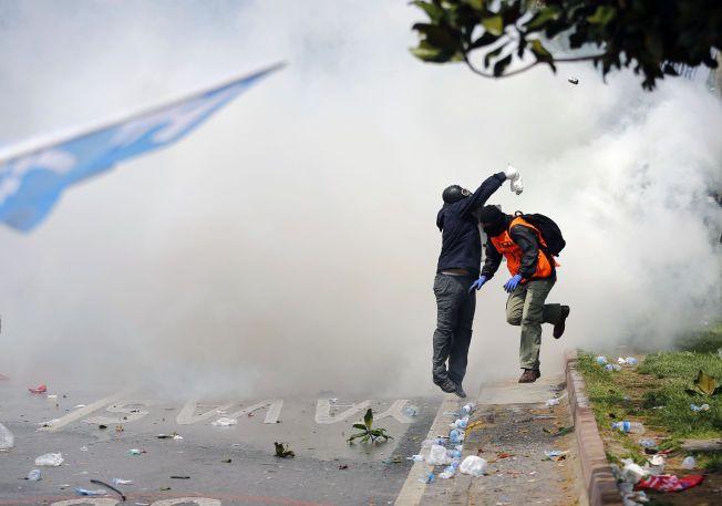 GASS: En demonstrant kaster gassbeholder tilbake på politiet under demonstrasjonene i Besiktas, Istanbul i dag. Demonstrantene ønsker å marsjere i Taksim, et område som politiet hadde stengt av for demonstranter.