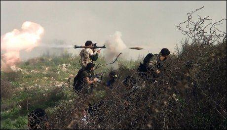 KAMPER: Opprørere skyter mot regjeringsstyrker under sammenstøt ved det strategisk viktige Khanasser-området, hvor den eneste veien som forbinder Aleppo med sentrale Syria ligger. Foto: AFP