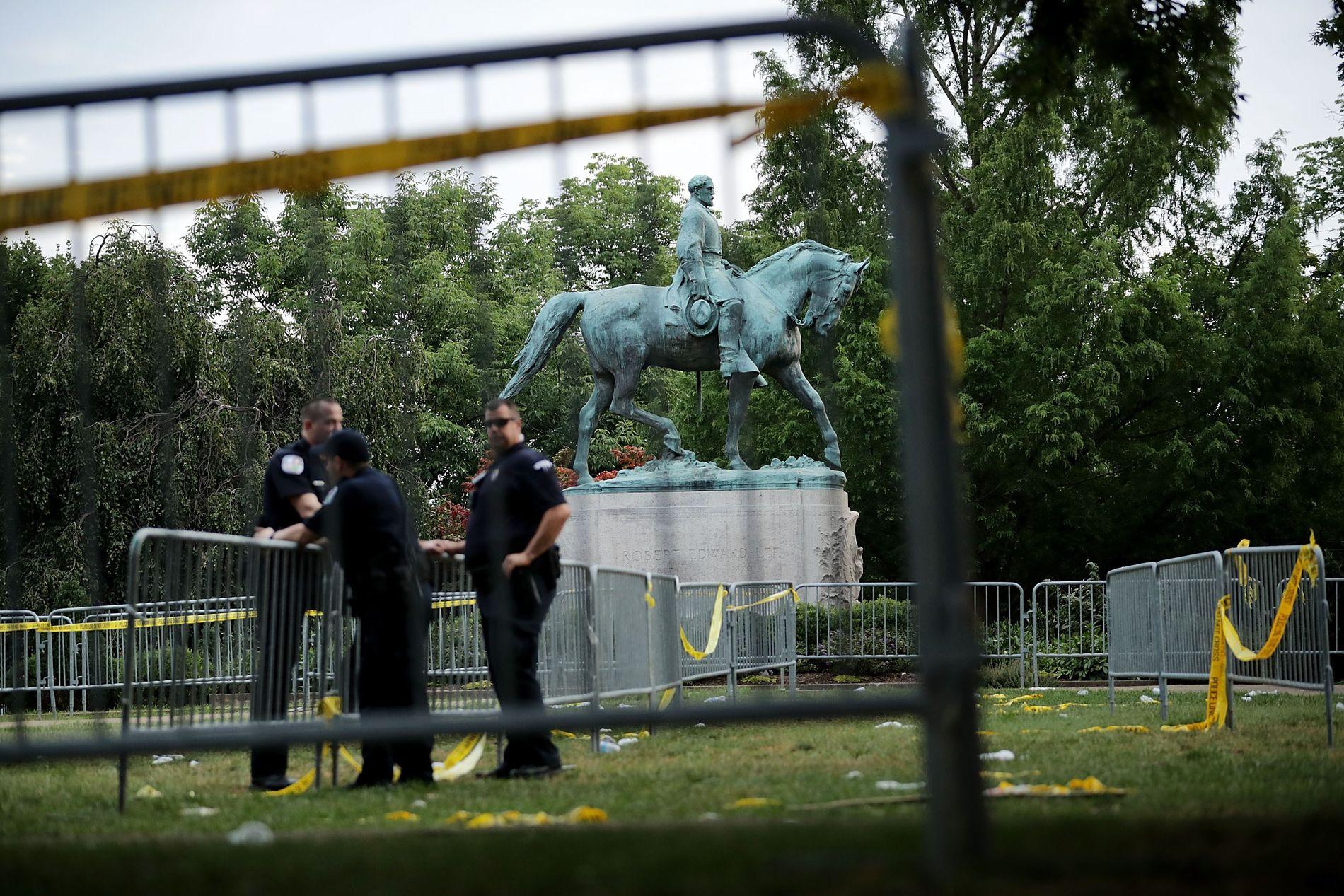 OMSTRIDT: Politiet i Charlottesville holder vakt ved statuen av sørstatsgeneralen Robert E. Lee, som utløste opptøyene i helgen. Foto: AFP
