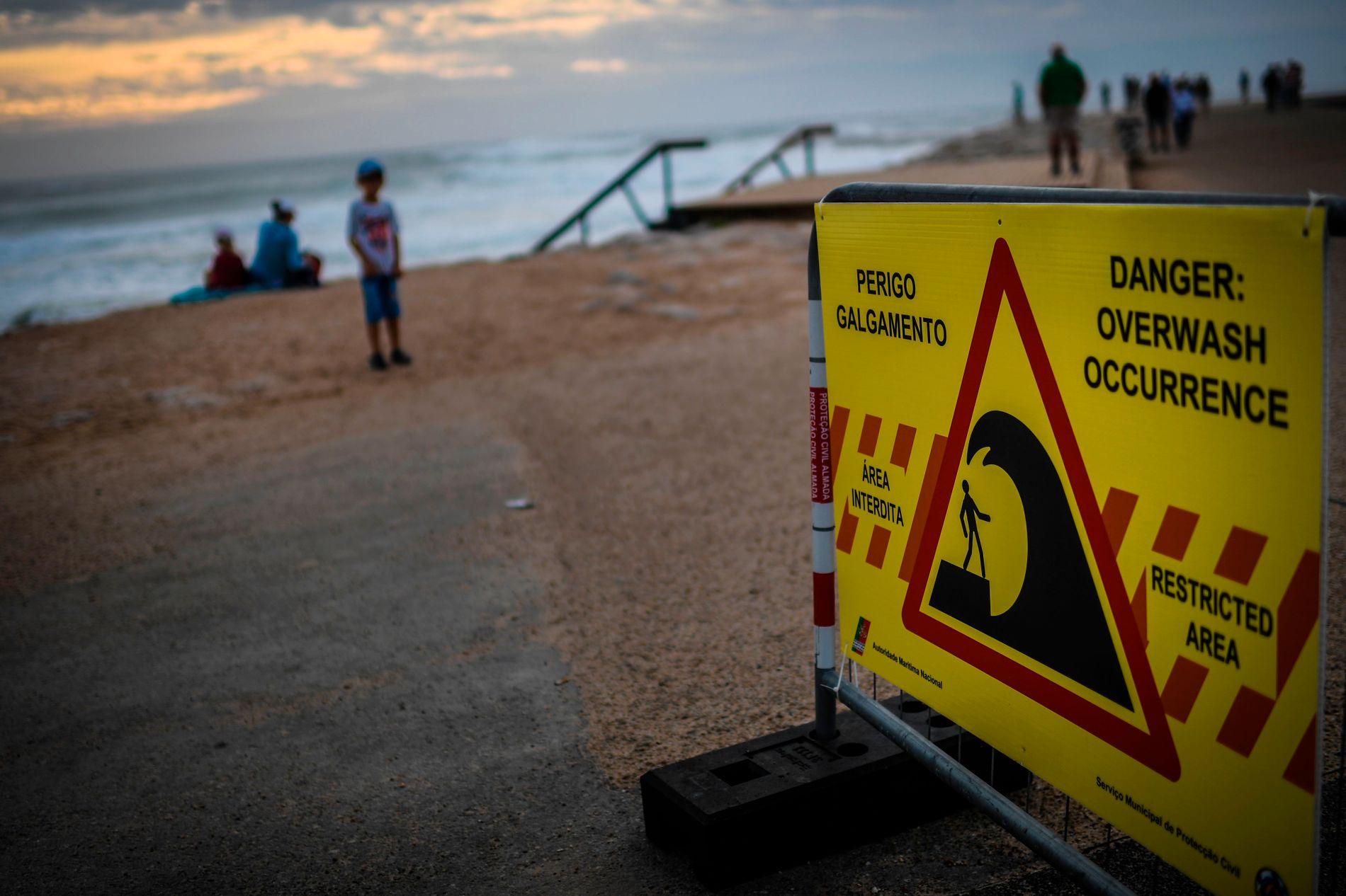 ADVARER: En advarsel-skilt på Costa da Caparica i nærheten av Lisboa lørdag. Størstedelen av landet er i «rød» beredskap.