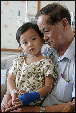 TRYGT: Flere barn har funnet tilbake til familien sin. Dette er Tan Wei En (3) fra Singapore med bestefar. Treåringens far er fortsatt igjen i Phuket for å lete etter moren til jenta. Foto: REUTERS