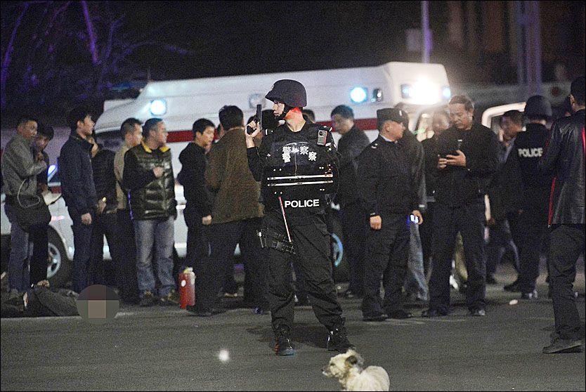 PÅ ÅSTEDET: En politimann står vakt i nærheten av en mann som ble skutt og drept av politiet, etter at en gruppe væpnede menn angrep folk på Kunming jernbanestasjon i Yunnan-provinsen i Kina. Foto: REUTERS