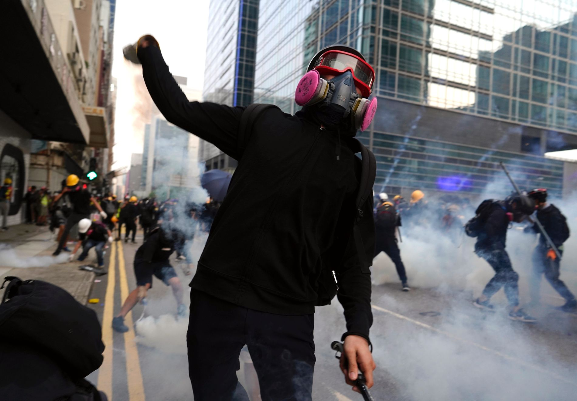 MOT POLITIET: Demonstranter i Hongkong kastet bensinbomber og murstein mot politiet lørdag. Etter demonstrasjonene ble 10 kvinner og 19 menn pågrepet.